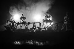 Oil pump oil rig energy industrial machine for petroleum, Group oil rigs and brightly lit industrial site at night. Toned.Backgrou. Nd for design. Selective Stock Images