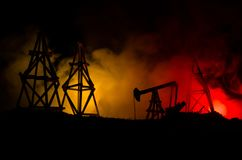 Oil pump oil rig energy industrial machine for petroleum, Group oil rigs and brightly lit industrial site at night. Toned.Backgrou. Nd for design. Selective Stock Image
