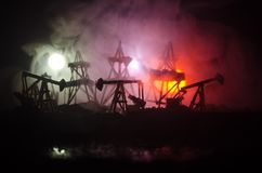 Oil pump oil rig energy industrial machine for petroleum, Group oil rigs and brightly lit industrial site at night. Toned.Backgrou. Nd for design. Selective Royalty Free Stock Images
