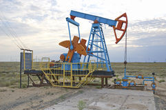 Oil pump. Old oil pump against clouds, Kazakhstan Stock Images