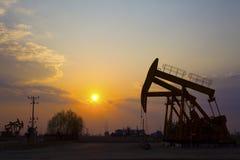 Oil Pump on orange sunset Royalty Free Stock Image