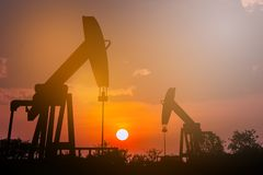 Oil pump oil rig energy industrial machine for petroleum in the. Sunset background for design royalty free stock photo