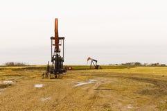 Oil pump in Saskatchewan, Canada. An oil pump on a muddy gravel pad in Saskatchewan, Canada Stock Photo