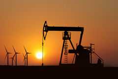 Oil pump silhouette in sunset. Oil pump silhouette and alternative energy in a sunset background Royalty Free Stock Photos