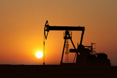 Oil pump silhouette in sunset. With oil tank Royalty Free Stock Photo