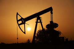 Oil pump and Sun at sunset. Oil pump silhuette and the Sun at sunset Royalty Free Stock Photo