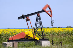 Oil pump with sunflowers field. On the background Royalty Free Stock Photo