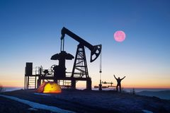 Oil pump at sunrise. In the Ukrainian Carpathians, the classical technology of oil and gas extraction by electric pumps against the background of the eternal Stock Images