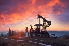 Oil pump at sunrise. In the Ukrainian Carpathians, the classical technology of oil and gas extraction by electric pumps against the background of the eternal Royalty Free Stock Photos