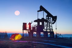 Oil pump at sunrise. In the Ukrainian Carpathians, the classical technology of oil and gas extraction by electric pumps against the background of the eternal Stock Photos