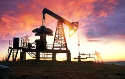 Oil pump at sunrise. In the Ukrainian Carpathians, the classical technology of oil and gas extraction by electric pumps against the background of the eternal Stock Photography