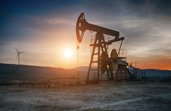 Oil pump on sunset. Oil pump on orange sunset royalty free stock photo