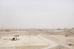 Oil pump and vast outcrop of  Bahrain oil field Royalty Free Stock Images
