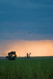 Oil pump in the west. Oil pump jack at sunset in west Texas, near Lubbock.  Cloud bank overhead Stock Image