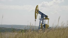 Oil pump working in the wheat field with hills in background - stock footage