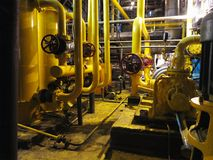 Oil pump, yellow pipes, tubes, machinery at power plant. Oil pump, yellow pipes, tubes, machinery at electric power plant stock photo