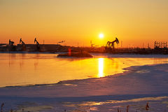 The oil pumping on the lakeside sunrise Royalty Free Stock Photography