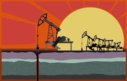 Oil pumping unit  against sunset. Royalty Free Stock Images