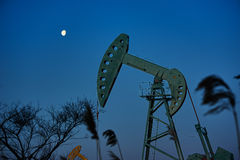 The oil pumping units and moon sunrise Stock Photo