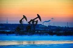 The oil pumping units sunset Stock Photos
