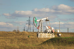 Oil pumpjack among grassy field at sunny day. Telephoto Royalty Free Stock Photography