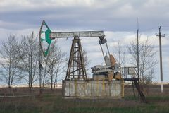 Oil pumpjack among grassy field at sunny day. Telephoto Stock Photos