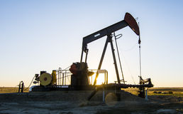 Oil Pumpjack - Oil and Gas Industry. An Oil Pumpjack at dusk in Alberta, Canada Royalty Free Stock Photo