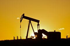 Oil Pumpjack in Sunset. An oil pumpjack silhoutted in the sunset Royalty Free Stock Photo