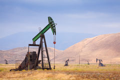 Oil Pumps At Large Oilfield In Huge Mountains Royalty Free Stock Image