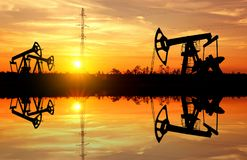 Oil Pumps. On the bank of the lake on a sunset Royalty Free Stock Images