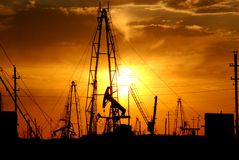 Oil pumps, derricks at sunset royalty free stock photos
