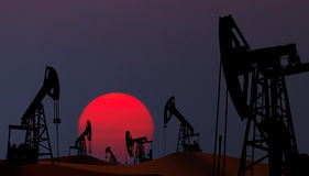 Oil pumps in desert. Oil pumps silhouette at  sunset Stock Images