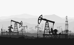Oil pumps at large oilfield over mountain range. Stock Photography