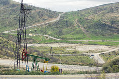 Oil pumps at large oilfield over mountain range. An oil well servicing rig sets up in mountainous country. Royalty Free Stock Photography