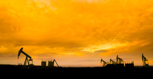 Oil pumps at oil field with sunset sky background Royalty Free Stock Images