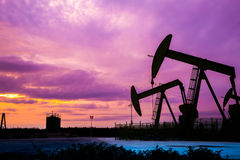 Oil pumps at oil field with sunset sky background Stock Photography