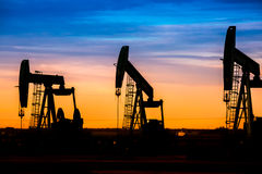 Oil pumps at oil field with sunset sky background Royalty Free Stock Photography