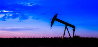 Oil pumps at oil field with sunset sky background Stock Photos