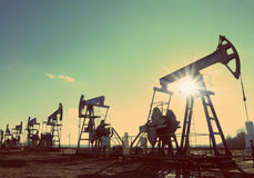 Oil pumps silhouette against sun - vintage retro style royalty free stock photography