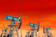 Oil pumps at sunset. Orange sky. Royalty Free Stock Image