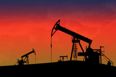 Oil pumps in the sunseth. Silhouette Oil pumps in the sunseth Stock Image