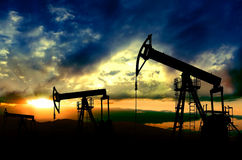 Oil pumps working on sunset background Stock Images