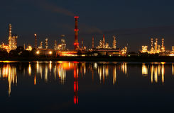 Oil refinery. A view of a large illuminated oil refinery at night with its lights reflected on the river Stock Photos
