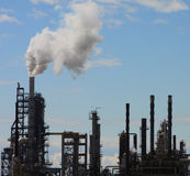 Oil Refinery Blue Sky. Oil refinery smokestacks and towers billowing smoke into the sky stock photography