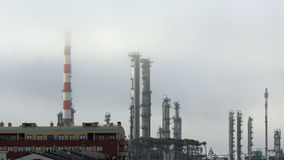 Oil refinery chimneys in the fog Royalty Free Stock Photo