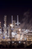 Oil refinery complex. An oil refinery in the United States with a series of foggy and smoky stacks. glowing lit up smoke stacks Royalty Free Stock Image