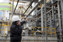 Oil refinery engineer. Pointing against pipeline Royalty Free Stock Photography