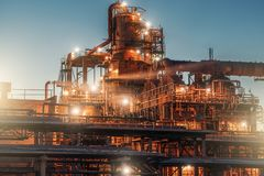Oil refinery factory in night, steel towers, vats and pipeline, modern production of energy and petroleum concept. Toned royalty free stock photos