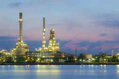 Oil refinery factory river front, twilight Stock Photo