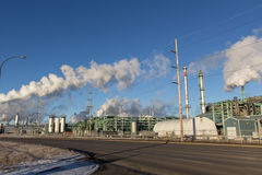 Oil refinery. Factory towers blowing steam Royalty Free Stock Photos